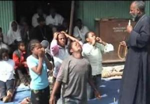 An excerpt of an exorcism video shows Father Girma speaking to allegedly possessed children (Youtube)